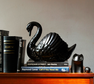 black ceramic swan on books